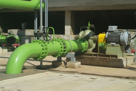 Pumps, valves and green steel pipes at industrial cooling tower.