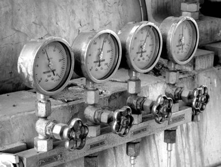 enhanced: Four industrial pressure meters in dirty industrial environment. Black and white photo with enhanced contrast.