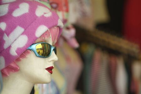 two and two thirds: Old, worn mannequin with pink and white cap, sunglasses and deep red lipstick. Blurry, out-of-focus shop-background in the right two thirds of the photo. Stock Photo