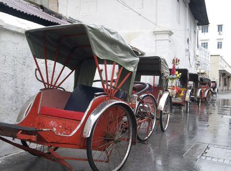 Trishaws waiting in the rain in Georgetown, Penang, Malaysia Standard-Bild
