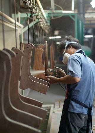 lopende band: Fabrieksarbeider spuiten meubilair delen op een assemblagelijn