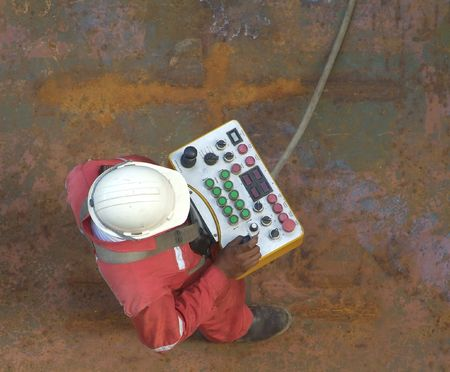 Man wearing a construction workers helmet with remote control, standing on a rusty steel deck.