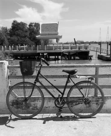 chao praya: Old bicycle waiting at a quay along the Chao Praya river in Samut Prakan, Thailand. Black and white photo with background out of focus. Stock Photo
