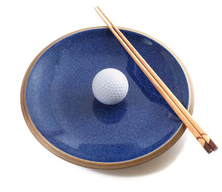 Blue plate with golf-ball and chop sticks. Isolated on white background. Stock Photo