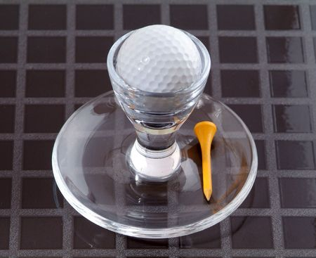 Golf-ball in an eggcup, with a yellow tee.