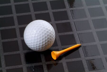 Golf ball and yellow, wooden tee on a checkered, black background Stock Photo