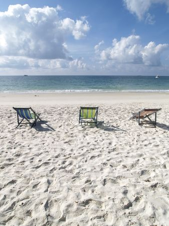 Three chairs on the white sand beach of Koh Samet in Rayong province, Thailand
