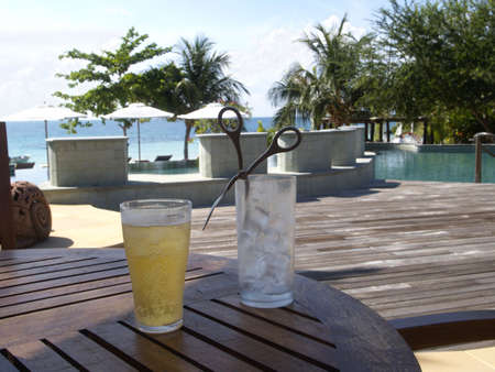 Glass of beer and ice-cubes in the shadow at tropical luxury, beach resort. Stock Photo