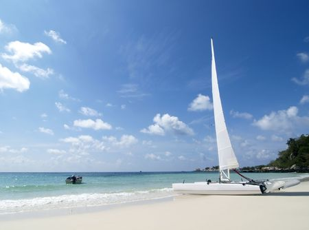 Catamaran sailboat on a white, tropical beach on a sunny day at Koh Samet in Rayong province, Thailand