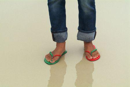 Los pies de una mujer en una playa h�meda. El pie derecho lleva una sandalia verde, el rojo y el pie izquierdo, con las u�as de los pies pintadas de colores coincidentes, y que corresponden a los colores de las l�mparas de barco.  Foto de archivo - 898911