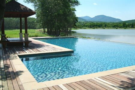 Swimming pool at the edge of a lake among mountains in Rayong province, Thailand.