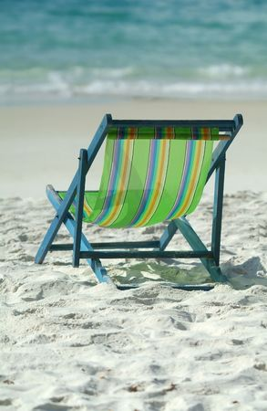 Green lawn chair on a sunny beach facing the ocean. Shallow depth of field with background out of focus. Stock Photo