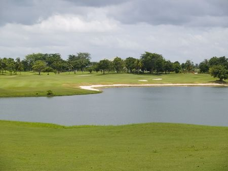 hindrance: Large water hindrance at a golf course. Fairway, trees and heavy, black clouds in the background.