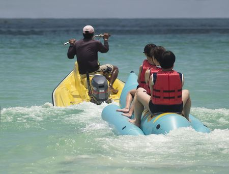 lifevest: Banana boat with passengers pulled by an old style water scooter, leaving the beach