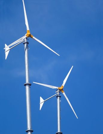 Two small wind turbines against a blue sky