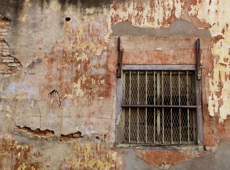 Window with steel bars of old brick building, lacking maintenance photo