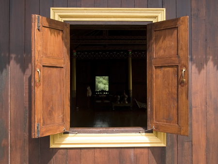 rear end: Open window on an old, wooden house. Dark room on the inside, with another opening at the rear end, where a lush garden can be seen. Stock Photo