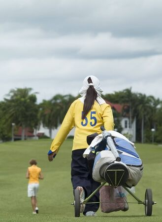 assistent: Caddie following a golf player down the fairway on a cloudy day. Caddie and bag in focus, player out of focus.