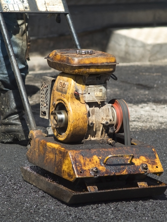 compactor: Old, worn, little compactor plate in use on tarmac. Stock Photo