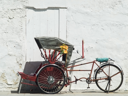 Red, Asian trishaw parked in front of a white concrete wall in Georgetown, Penang, Malaysia. Stock Photo - 1647036