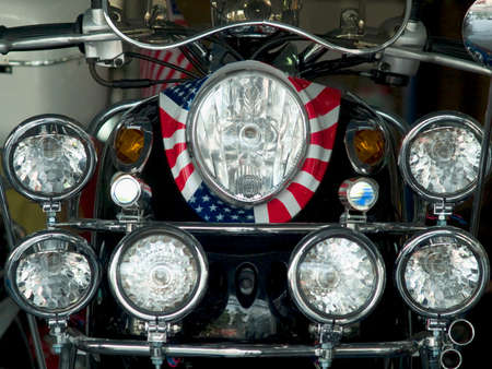 Detail of scooter with the pattern of the American flag wrapped around the headlight and lots of extra lights. photo