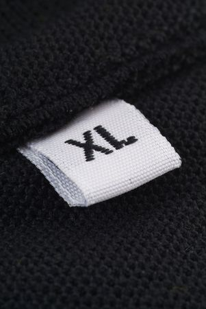 extra large: Clothing label with the size XL or Extra Large. Macro photography with extreme detail and shallow depth of field.