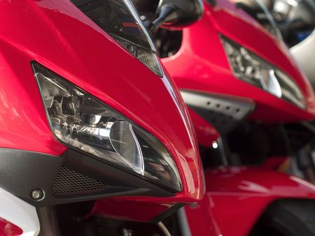 Details of two red motorbikes, one sharp in the foreground and one blurred in the background photo
