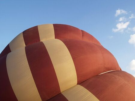 inflated: Detail of brown and beige hot-air balloon, halfway inflated. Stock Photo