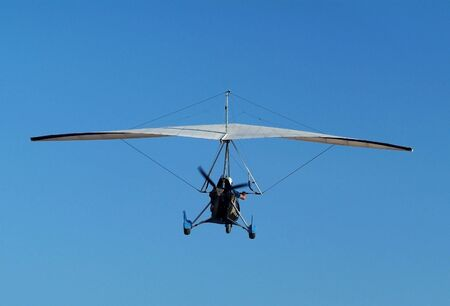depart: Microlight airplane airborne on a blue sky background