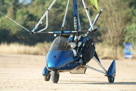 airfield: Blue microlight airplane on a dirt airfield