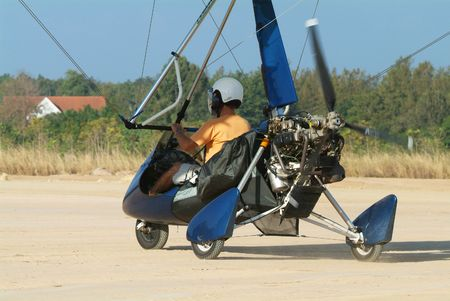 airfield: Microlight airplane taxiing down a dirt runway at an airfield