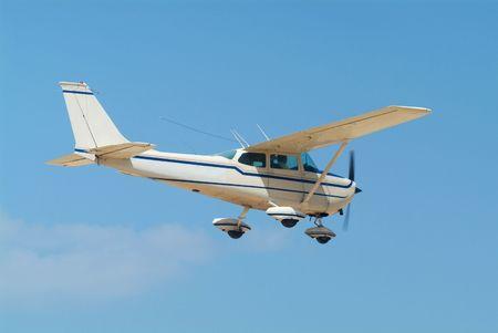 Light, white airplane mid-air on a blue sky background Standard-Bild