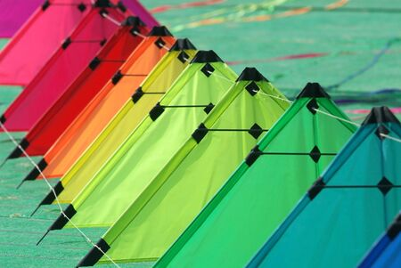 A string of colourful stunt kites on the ground, ready for take-off Stock Photo