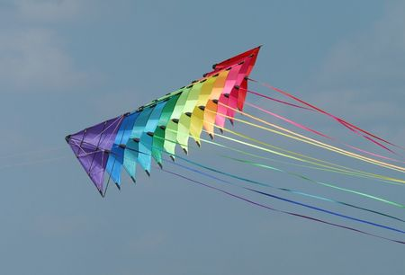 A string of colourful stunt kites with long tails on a cloudy sky background
