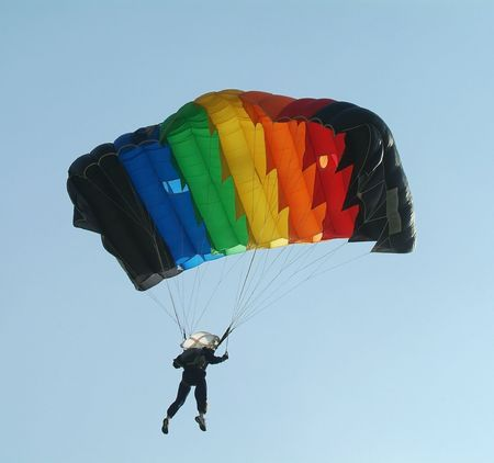 Parachutist with a colourful parachute seen from below on a blue sky background