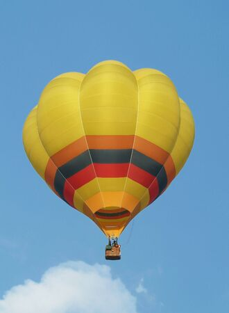 Yellow hot-air balloon flying mid-air. Blue sky background. Stock Photo