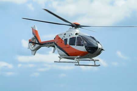 helicopter pilot: Orange and silver coloured helicopter flying above Stock Photo