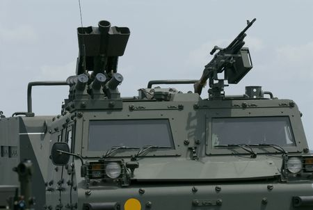 weaponry: Front detail of tracked military vehicle with weaponry on the roof.