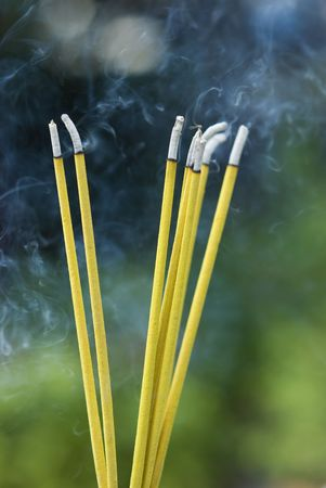Burning incense sticks at a Buddhist temple in Thailand. Shallow depth of field, with the background out of focus.
