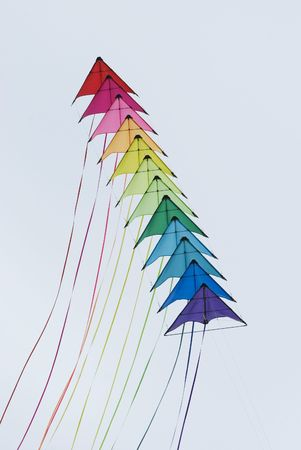 A string of colourful stunt kites on a grey sky background Stock Photo