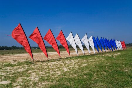 Red, white and blue flags on a field of grass, with a blue sky background. photo