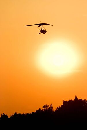 Silhoutte of microlight aircraft flying over the orange sunset.