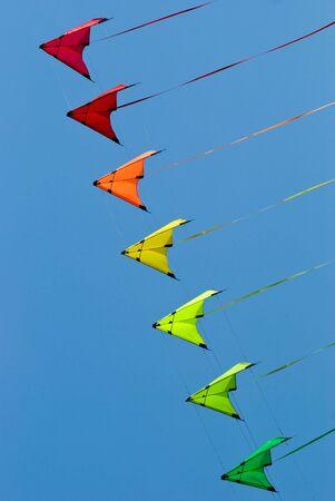 papalote: Pila de truco cometas en colores de arco iris sobre un cielo azul de fondo Foto de archivo