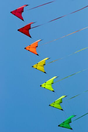 flying a kite: Stack of stunt kites in rainbow colours on a blue sky background