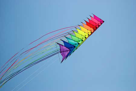 Stack of 12 stunt kites in rainbow colours on a blue sky background Stock Photo