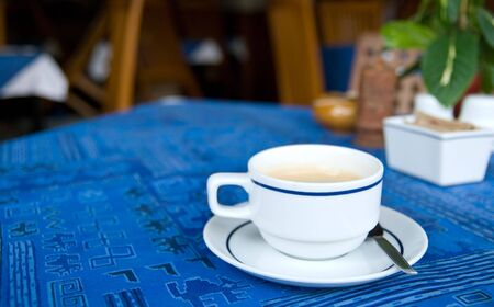 coffeebreak: Cup of coffee on a restaurant table with blue tablecloth. Shallow depth of field with only the cup in focus.