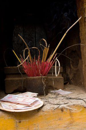 tran: Paper money and joss sticks at the Tran Quoc Pagoda in Hanoi, Vietnam. Stock Photo