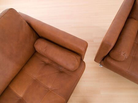 Detail of two brown leather sofa on a parquet floor photo