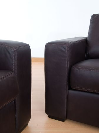 Details of two brown leather sofas with visible seams on a parquet floor and with a white wall behind. photo