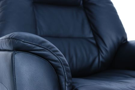 recliner: Detail of black leather recliner. Shallow depth of field, with only the armrest in focus.